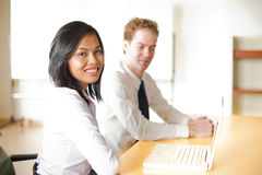 Beautiful Asian Business Woman Meeting. A cute corporate asian businesswoman smiles during a meeting with her caucasian colleague in front of a laptop Stock Photos