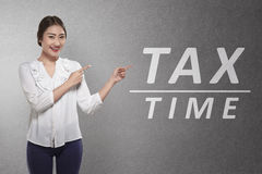 Beautiful asian business woman pointing Tax time word Royalty Free Stock Image