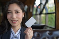 Beautiful asian business woman smile and holds blank white business or credit card isolated on white background. royalty free stock images