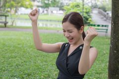 Beautiful asian business woman smiling and raising up two hands royalty free stock photography