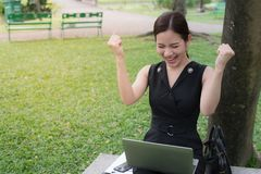 Beautiful asian business woman smiling and raising up two hands to celebrate for business successful. stock image