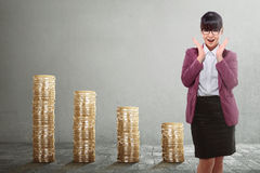 Beautiful asian business woman standing with golden stack coins Stock Photos