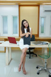 Beautiful Asian business woman standing at her desk in office.  Royalty Free Stock Photo