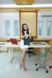 Beautiful Asian business woman standing at her desk in office Stock Photo