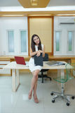 Beautiful Asian business woman standing at her desk in office.  Royalty Free Stock Images
