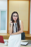Beautiful Asian business woman standing at her desk in office Royalty Free Stock Photos