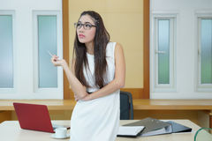 Beautiful Asian business woman standing at her desk in office Royalty Free Stock Photography