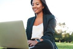 Beautiful asian business woman in suit using laptop computer in Royalty Free Stock Image
