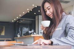 A beautiful Asian business woman touching and looking at tablet pc while drinking coffee Stock Photo