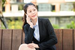 Beautiful asian business woman use smart phone on park bench Royalty Free Stock Photos