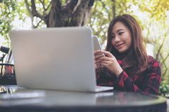 A beautiful Asian business woman using and looking at smart phone with laptop on glass table at outdoor Stock Photography