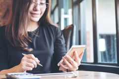 A beautiful Asian business woman working , holding notebook and using calculator Stock Photos