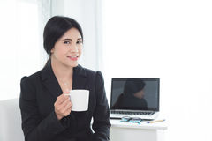 Beautiful businesswoman in black suit sitting and smiles Stock Photo