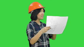 Beautiful asian businesswoman engineer holding the blueprint and wearing the safety helmet on a Green Screen, Chroma Key stock video