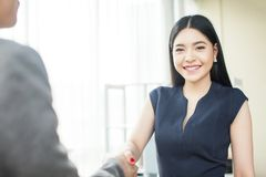 Beautiful Asian businesswoman smiling and shaking hands. With other businessman stock photo