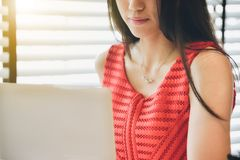 A beautiful Asian businesswoman wearing a red dress with her lap royalty free stock images