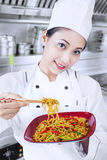 Asian chef and fried noodle in kitchen. Beautiful Asian chef cooks fried noodle in kitchen stock photography