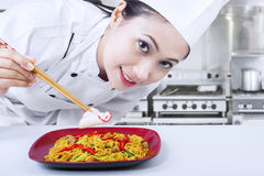 Asian chef prepare noodle at work. Beautiful Asian chef prepares fried noodle in kitchen royalty free stock photos