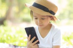 Beautiful asian child smiling using smart mobile phone in the garden, kid have passion playing game digital on smartphone. On internet network in the park with stock photo