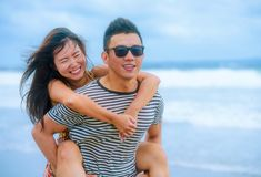 beautiful Asian Chinese couple with boyfriend carrying woman on her back and shoulders at the beach smiling happy in love Stock Photo
