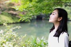 A happy free smile peace balance meditation beauty girl Asian Chinese travel hiking smell maple do yoga by lake bag hangzhou xihu Royalty Free Stock Photography