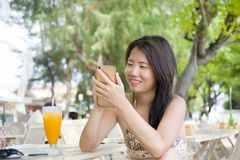 Beautiful Asian Chinese woman using internet social media on mobile phone sitting at beach restaurant resort enjoying summer holid. Young happy and beautiful Stock Photo