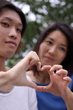 Beautiful Asian couple outside forming a heart Royalty Free Stock Image