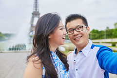 Beautiful Asian couple taking selfie in Paris. Beautiful Asian couple of tourists spending their vacation in Paris and taking selfie with a mobile phone with the stock images