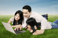 Beautiful Asian family use laptop in nature. Image of a joyful Asian family lying on the meadow while playing games with a laptop computer Royalty Free Stock Photos
