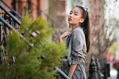 Beautiful asian fashionable young woman posing on city street outdoors. Royalty Free Stock Photos