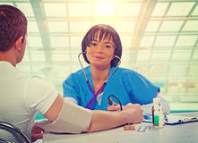 Beautiful asian female doctor sitting at the table with patient Royalty Free Stock Photos