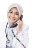 Beautiful asian female doctor talking on the phone. Close up portrait of beautiful asian female doctor talking on the phone isolated on white background Stock Photography