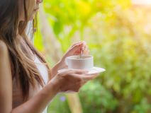 Beautiful asian female drinking a cup of coffee at the garden stock image