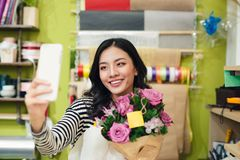Beautiful asian female florist holding bouquet of flower and taking selfie with mobile phone Royalty Free Stock Photos
