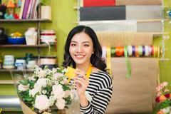 Beautiful asian female florist holding bouquet of flowers Stock Photos