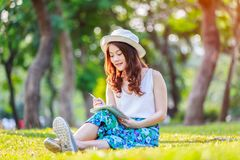Beautiful asian female hands with a pen writing notebook and she was sitting on grass outside Royalty Free Stock Photos