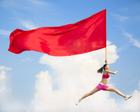 Beautiful Asian female jumping with big red flag royalty free stock photo