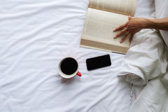 Beautiful asian female sitting on the bed with a cup of coffee and reading a book Stock Photo