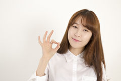 Beautiful asian female student giving okay sign Royalty Free Stock Photography