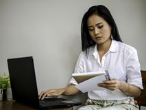Beautiful asian freelancer looking note book, typing on labtop keyboard concentrate her work royalty free stock photo