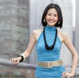 Beautiful Asian in front of Singapore skyline. A beautiful and successful Asian posing for a photo in front of skyscrappers in the business district of Singapore Royalty Free Stock Photos