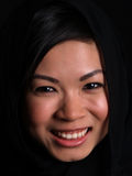Beautiful Asian girl. A Beautiful Asian girl smiling over black with a balck scarf over her head Royalty Free Stock Images