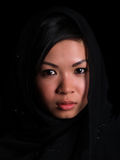 Beautiful Asian girl. A Beautiful Asian girl over black with a balck scarf over her head Stock Photography