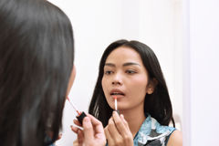 Beautiful asian girl applying lipstick while looking on the mirr Royalty Free Stock Photo