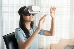 Free Beautiful Asian Girl Are Looking Through Vr Glasses To Play Games At Home, Woman Is Using Glasses With Virtual Reality Headsets At Stock Image - 152091361
