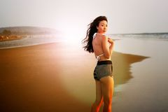Beautiful Asian girl in a bathing suit on the beach at sunset. stock images