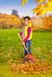Beautiful Asian girl with big red rake working Royalty Free Stock Image