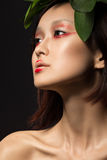Beautiful Asian girl with a bright make-up art in green leaves. Beauty face. Creative image. royalty free stock images