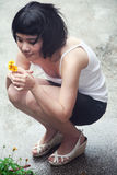 Beautiful Asian girl collecting flowers Royalty Free Stock Images