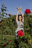 Beautiful Asian girl dancing among red roses Royalty Free Stock Photo